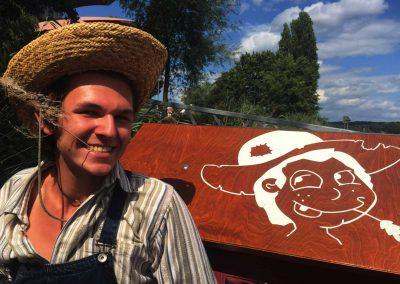 Mann mit Hut neben Huckleberrys Floß